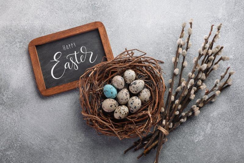Ovos da páscoa coloridos na caixa e nas flores na tabela imagens de stock royalty free