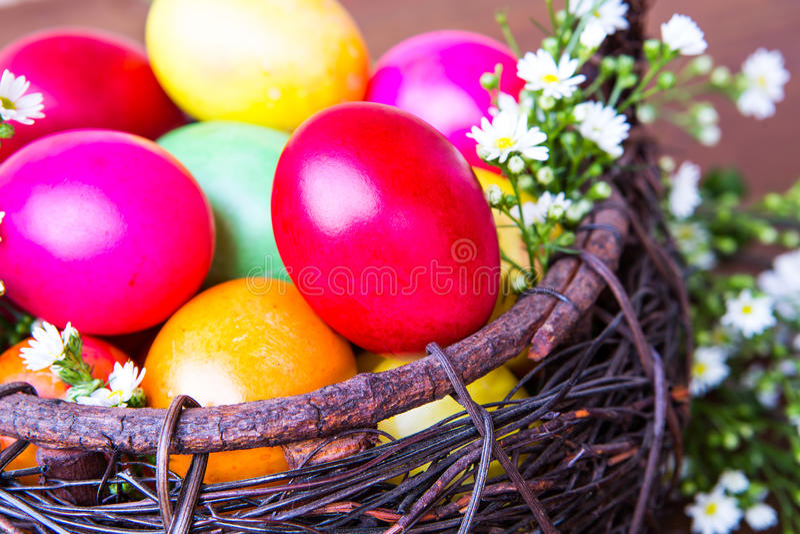 Ovos da páscoa coloridos na cesta marrom imagem de stock royalty free