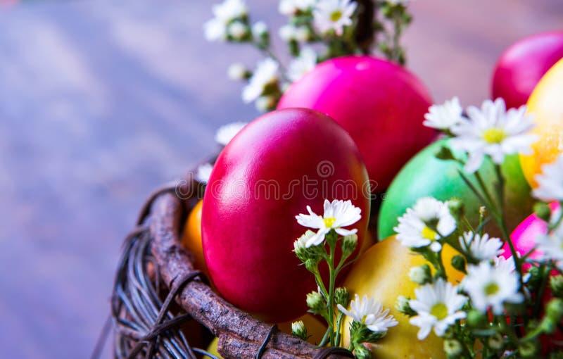 Ovos da páscoa coloridos na cesta marrom imagens de stock