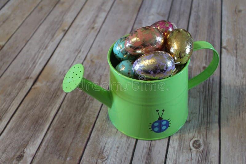 Ovos da páscoa coloridos na lata molhando fotografia de stock royalty free