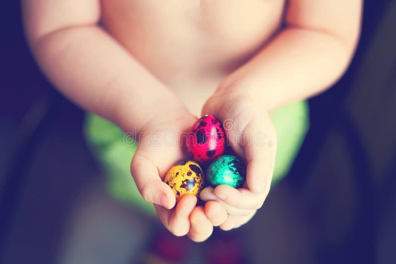 Ovos da páscoa coloridos nas mãos da criança após a ovo-caça imagens de stock royalty free