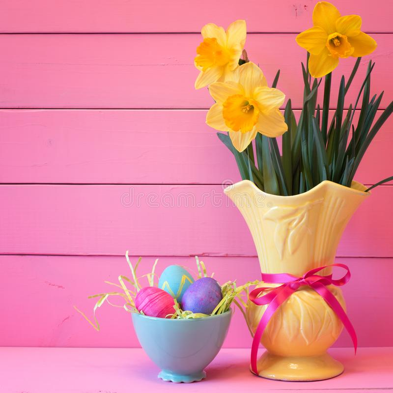 Ovos da páscoa coloridos no ninho com os narcisos amarelos no vaso no fundo cor-de-rosa das placas com sala ou no espaço para a c imagem de stock