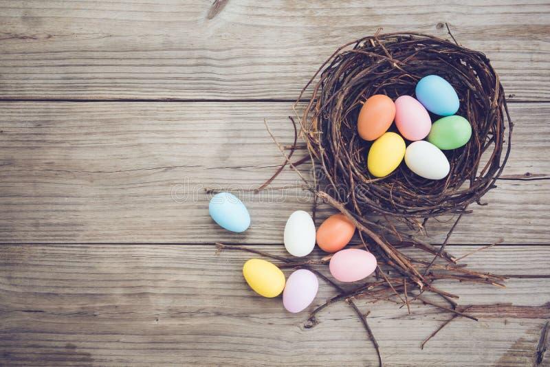 Ovos da páscoa coloridos no ninho no fundo de madeira rústico das pranchas imagem de stock