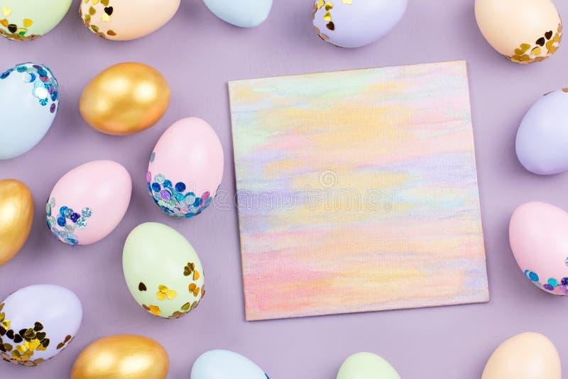 Ovos da páscoa coloridos pasteis decorados nas lantejoulas no fundo pastel, espaço da cópia Cartão feliz da Páscoa imagens de stock
