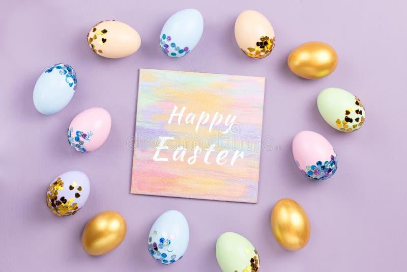 Ovos da páscoa coloridos pasteis decorados nas lantejoulas no fundo pastel, espaço da cópia Cartão feliz da Páscoa imagens de stock royalty free