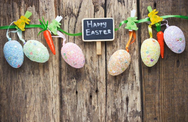 Ovos da páscoa coloridos que penduram no fundo de madeira rústico com sp fotografia de stock royalty free