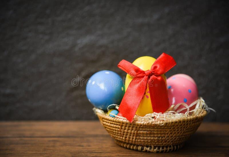 Ovos da páscoa com curva vermelha da fita na cesta do ninho no fundo de madeira e escuro rústico da tabela imagens de stock royalty free