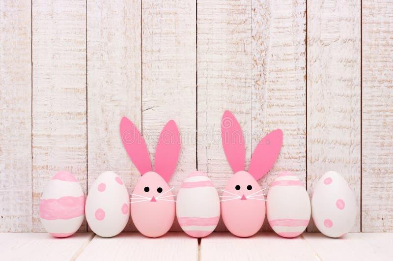 Ovos da páscoa contra a madeira branca, dois com caras do coelho e orelhas foto de stock royalty free