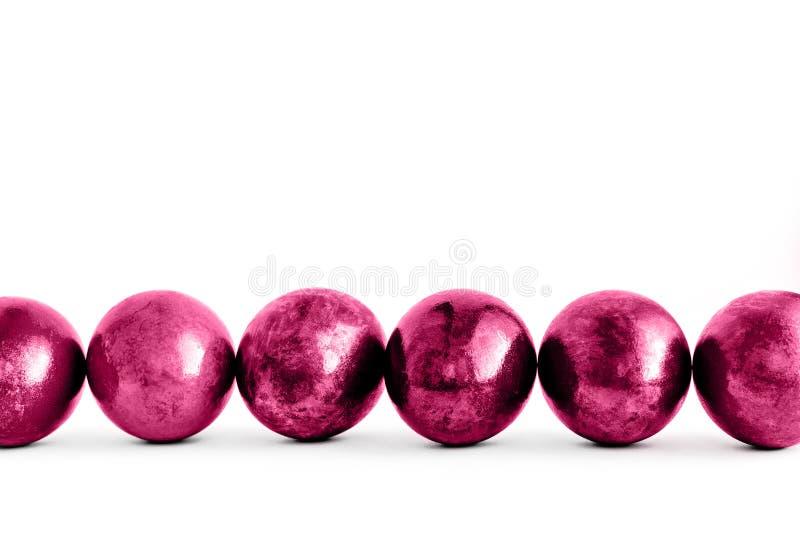 Ovos da p?scoa cor-de-rosa na moda alinhados no fundo branco Close-up imagem de stock royalty free