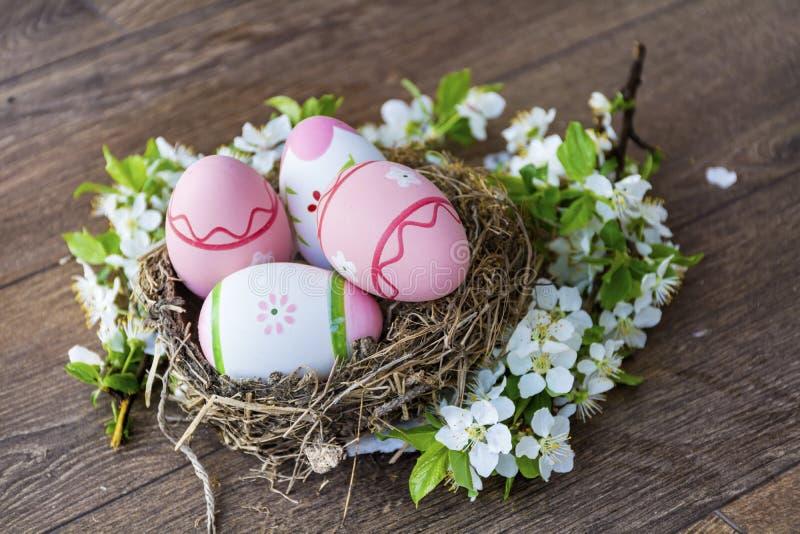 Ovos da páscoa cor-de-rosa no ninho real com flores de cerejeira em um fundo de madeira foto de stock