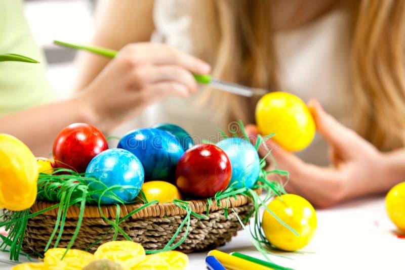 Ovos da páscoa da pintura das crianças em casa. imagem de stock royalty free