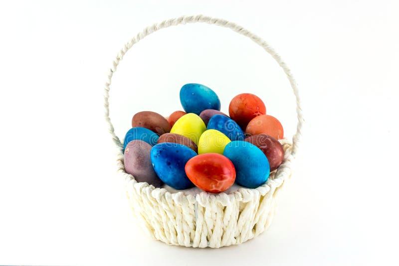 Ovos da páscoa de Colorfull na cesta de vime isolada no fundo branco fotografia de stock