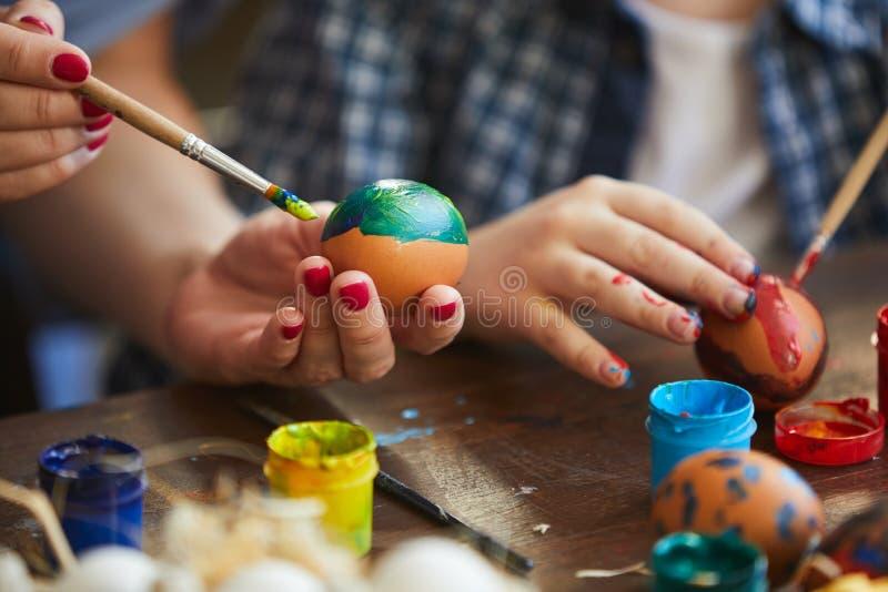 Ovos da páscoa de pintura da mãe e da criança fotos de stock