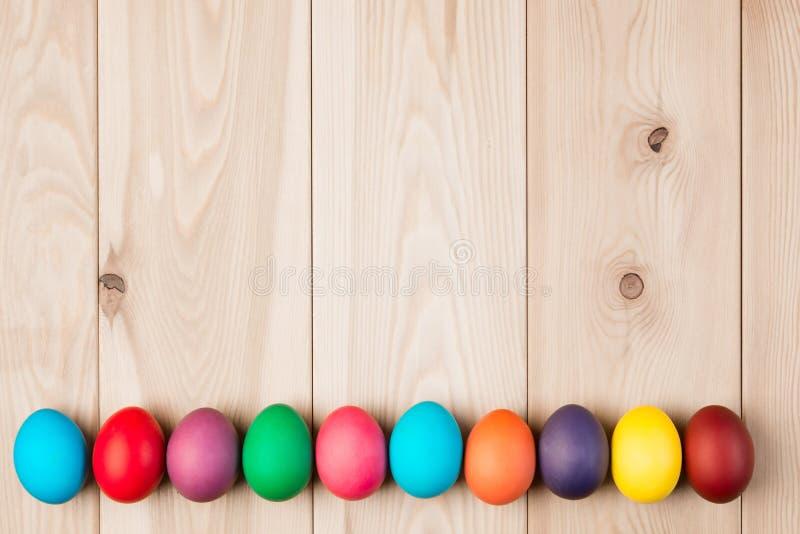 Ovos da páscoa de uma série e um fundo de madeira imagem de stock