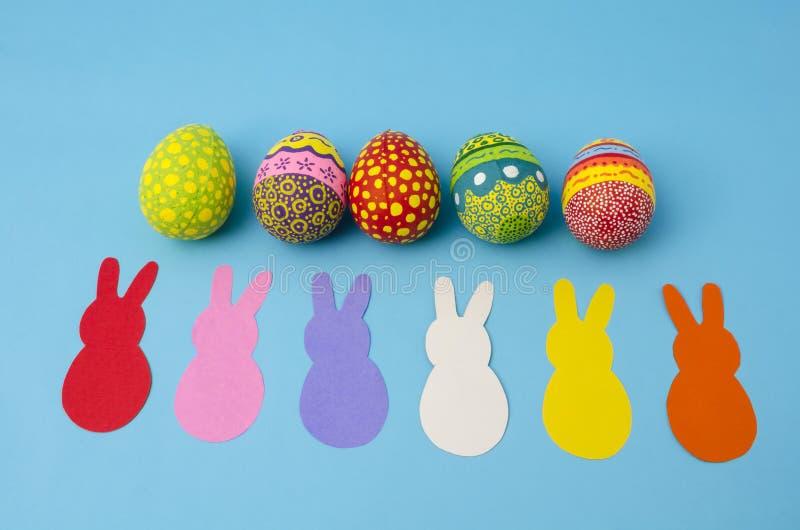 Ovos da páscoa decorados coloridos e coelhos de papel coloridos fotografia de stock