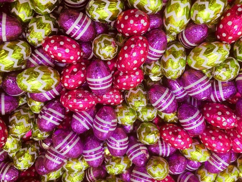 Ovos da páscoa do chocolate no envolvimento colorido da folha imagem de stock royalty free