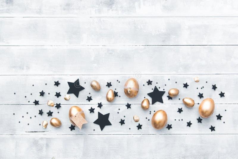 Ovos da páscoa dourados da vista superior sobre o fundo de madeira foto de stock