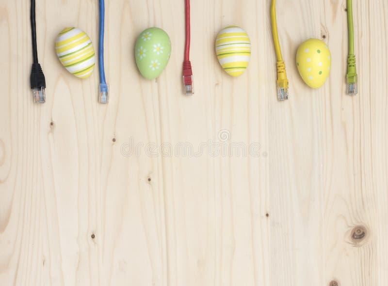 Ovos da páscoa e cabos do Internet na placa de madeira fotos de stock royalty free