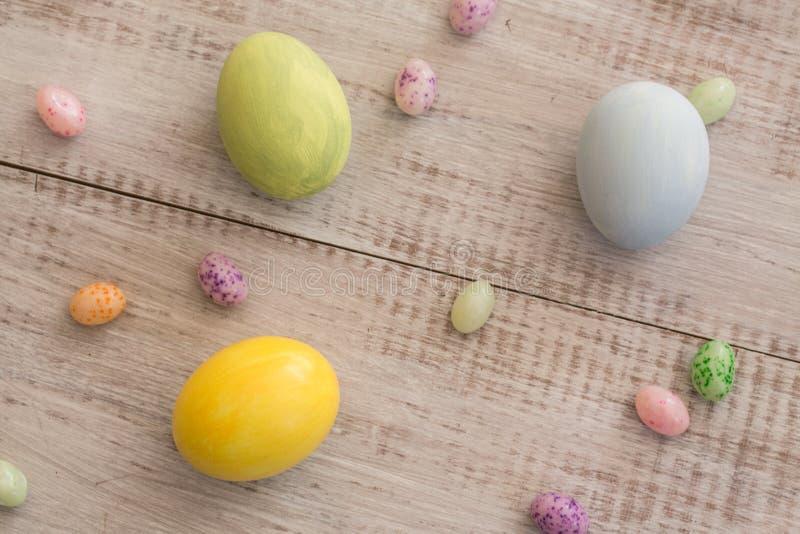 Ovos da páscoa e Jelly Beans coloridos cor pastel em Backgro de madeira branco imagem de stock royalty free