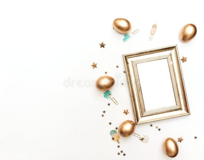 Ovos da páscoa e quadro colocados lisos do ouro no fundo branco foto de stock royalty free