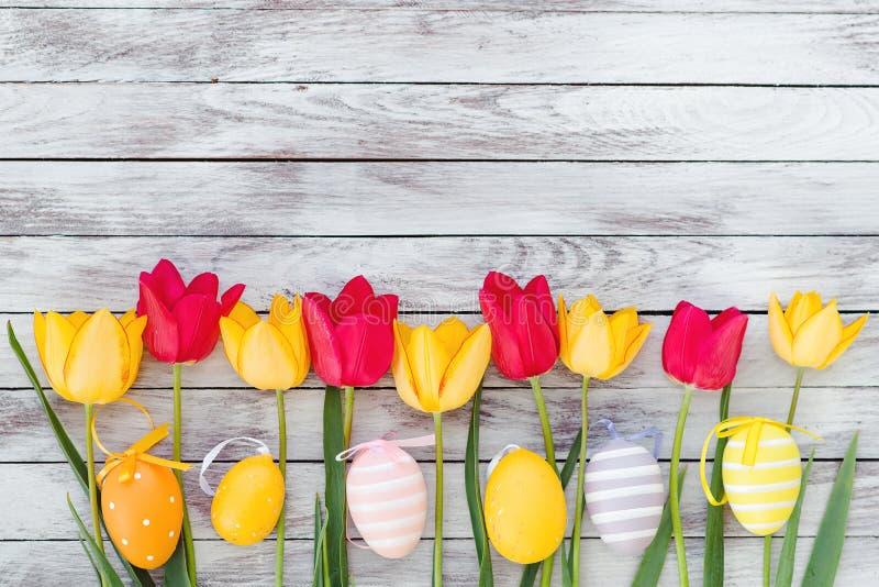 Ovos da páscoa e tulipas coloridos em pranchas de madeira fotografia de stock