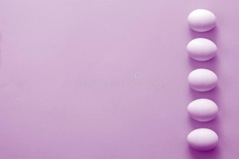 Ovos da páscoa e tulipas das flores no fundo roxo De cima de, espaço da cópia, configuração lisa imagem de stock