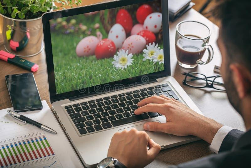 Ovos da páscoa em um tela de computador Homem que trabalha em seu escritório imagens de stock royalty free