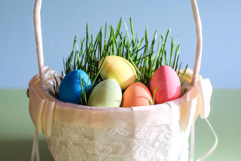 Ovos da páscoa em uma cesta branca bonita com grama verde foto de stock royalty free