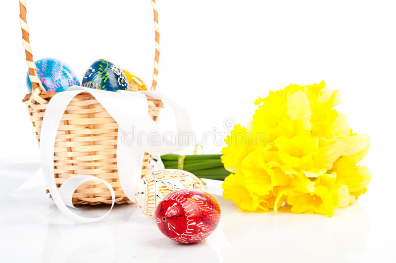 Ovos da páscoa em uma cesta e em flores fotografia de stock royalty free