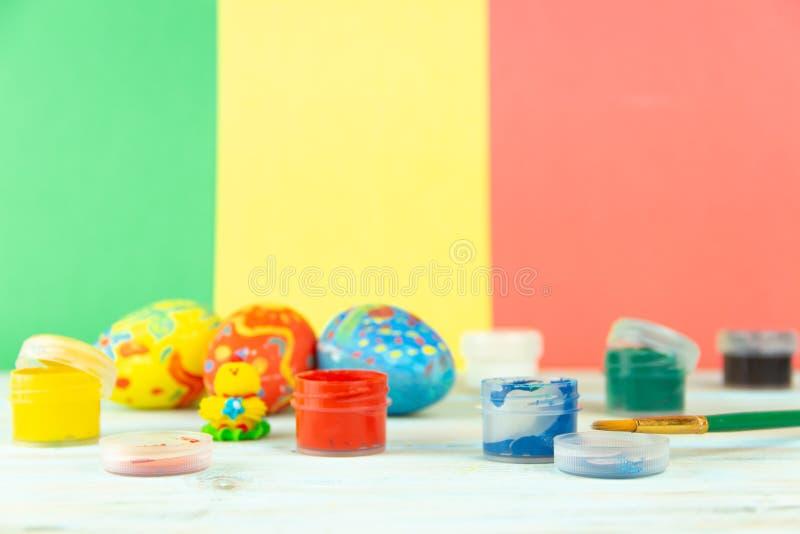 Ovos da páscoa feitos a mão no fundo de madeira multicolorido com pinturas e escova imagens de stock