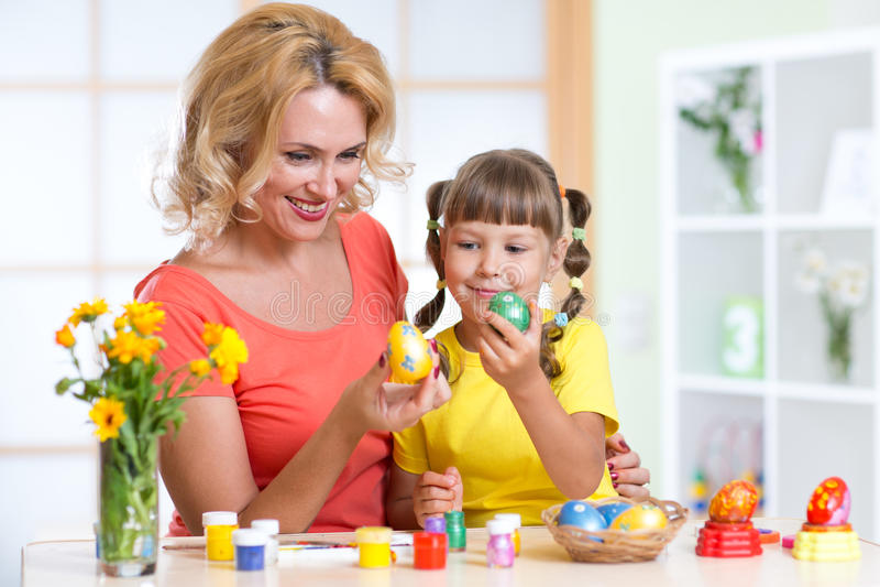 Ovos da páscoa felizes da pintura da mãe e da criança imagens de stock