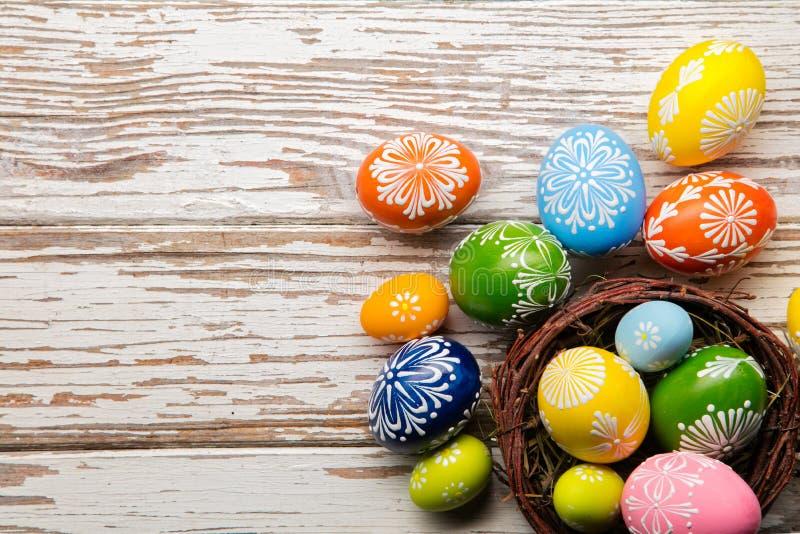 Ovos da páscoa na cesta colocada em pranchas de madeira fotografia de stock