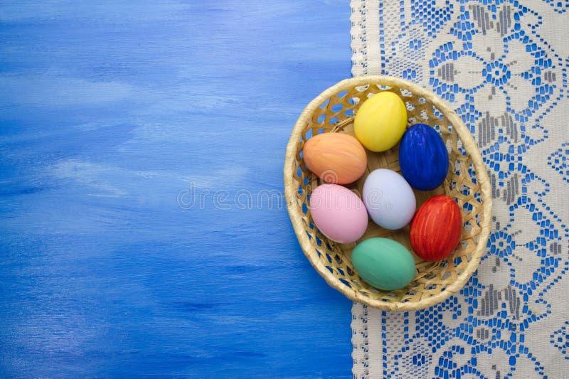 Ovos da páscoa na cesta do yello nos fundos S1V6 do azul e da tela fotos de stock