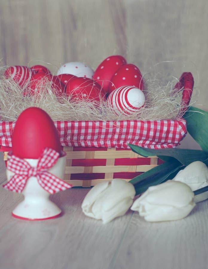 Ovos da páscoa na cesta e nas tulipas brancas imagem de stock royalty free