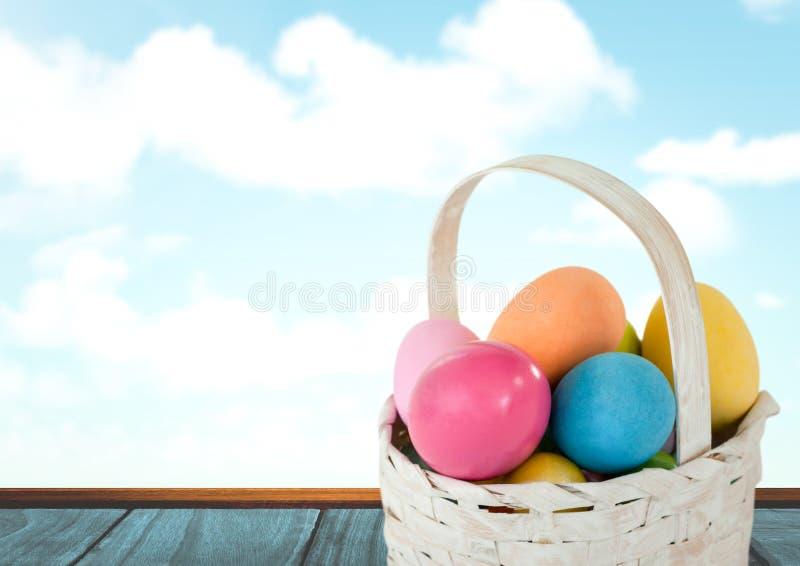 Ovos da páscoa na cesta na frente do céu azul ilustração royalty free
