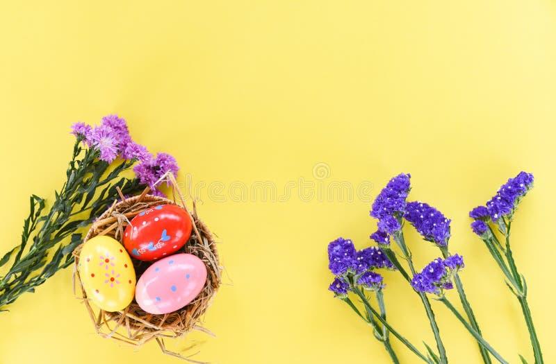 Ovos da páscoa na decoração do ninho da cesta com as flores roxas do Marguerite e do statice da flor no fundo amarelo fotos de stock