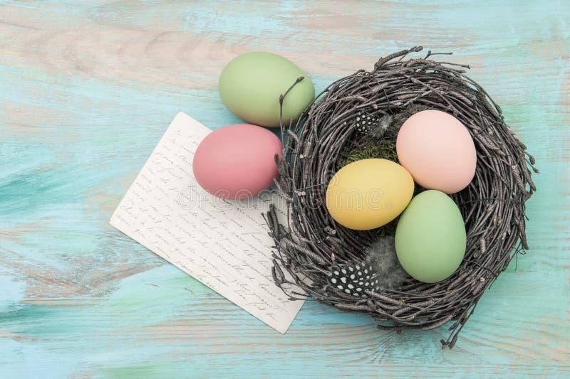 Ovos da páscoa no cartão de cumprimentos do ninho e da antiguidade fotos de stock