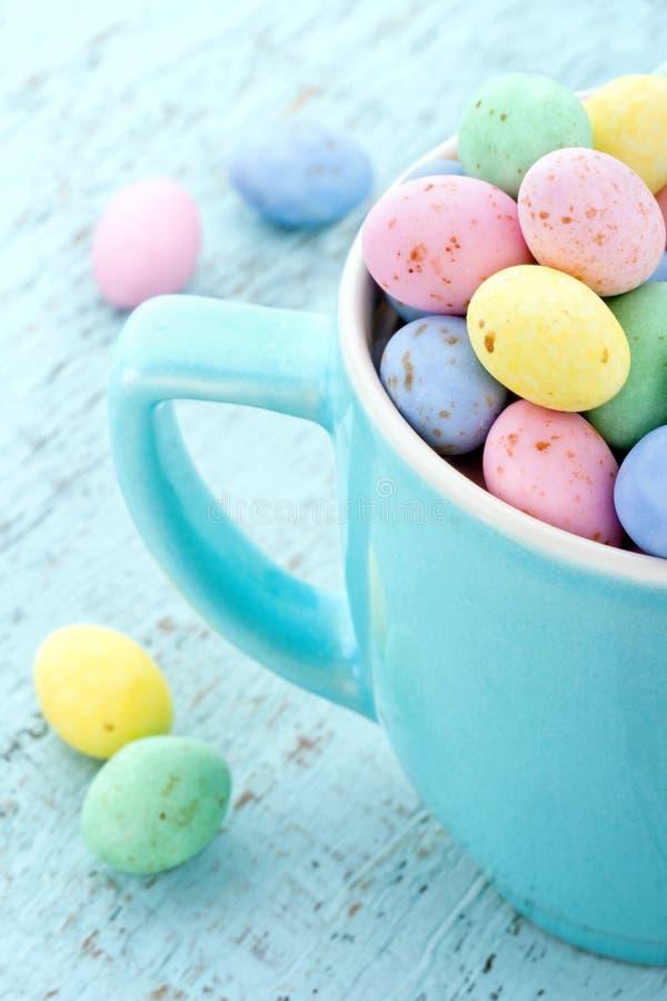 Ovos da páscoa Pastel em uma luz - copo azul fotografia de stock