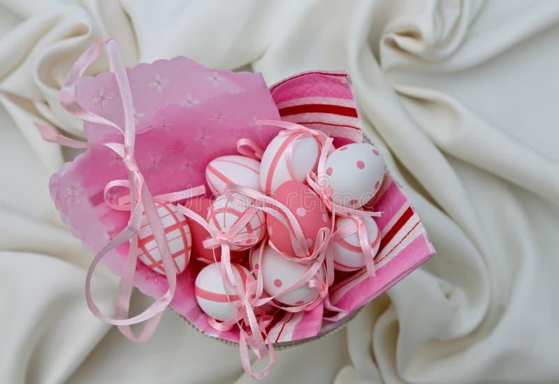 Ovos da páscoa pequenos do rosa e os brancos em um fundo branco de matéria têxtil fotos de stock