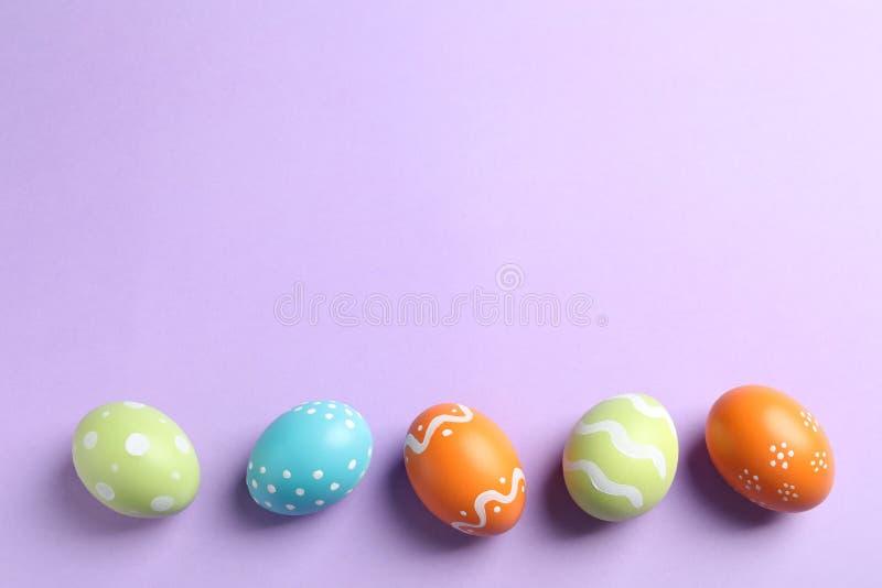 Ovos da páscoa pintados bonitos no fundo da cor, configuração lisa imagem de stock royalty free