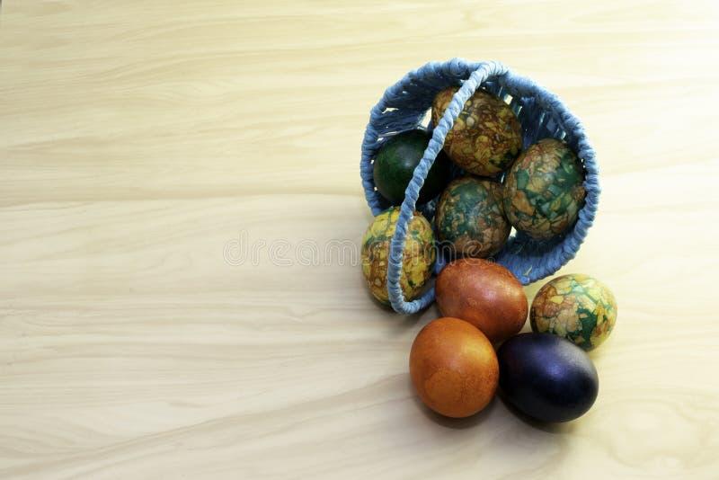 Ovos da páscoa que encontram-se em uma tabela de madeira amarela e em uma cesta azul, pastas da cópia foto de stock royalty free