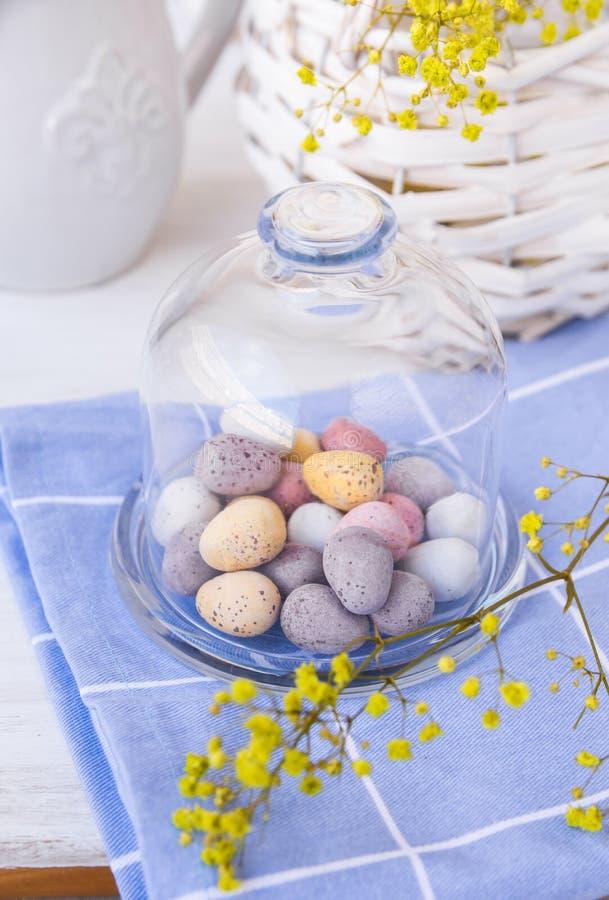 Ovos da páscoa salpicados coloridos do chocolate no frasco de sino de cristal no guardanapo azul na tabela branca, cesta com flor foto de stock