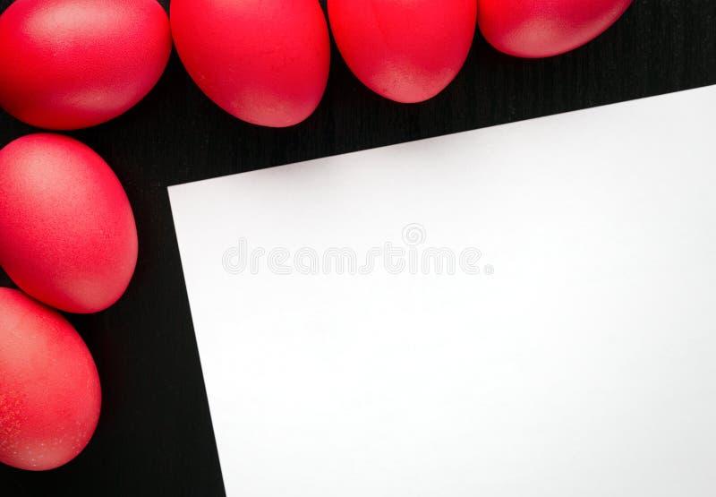 Ovos da páscoa vermelhos, em um fundo de madeira preto O conceito da fotografia de stock