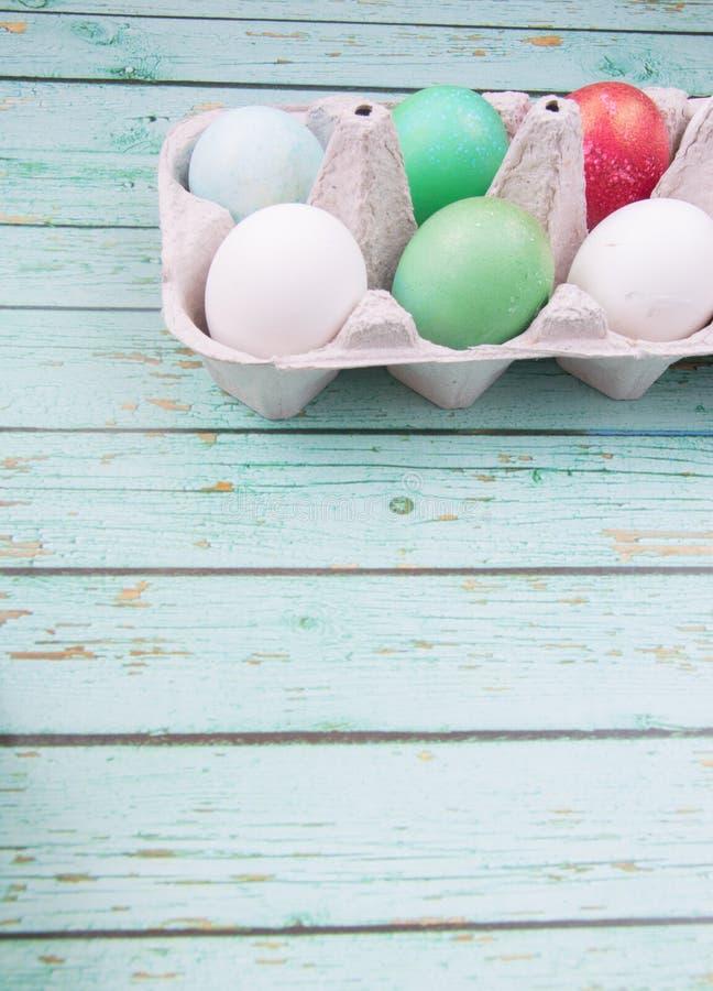 Ovos da páscoa vermelhos, multicoloridos, alaranjados e verdes no fundo de madeira azul foto de stock