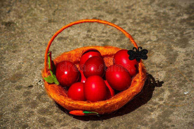 Ovos da páscoa vermelhos na cesta marrom imagem de stock