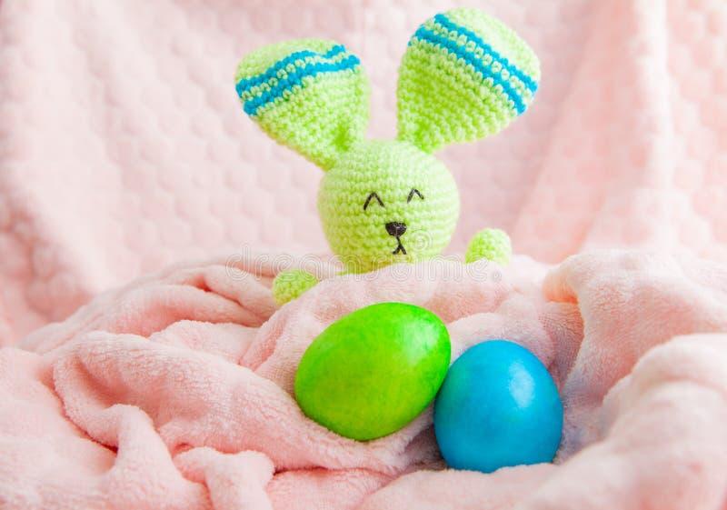 Ovos da p?scoa e brinquedo coloridos bonitos do coelho Conceito da P?scoa em uma manta macia imagens de stock royalty free