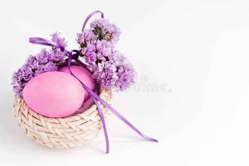 Ovos da p?scoa na cesta decorada com as flores em tons lil?s no fundo branco ano novo feliz 2007 imagem de stock royalty free