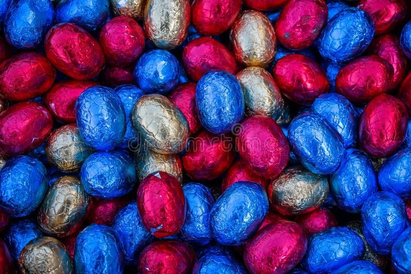 Ovos de chocolate coloridos e envolvidos de easter imagens de stock royalty free
