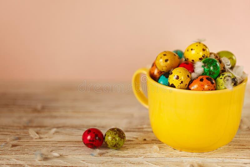 Ovos de codorniz coloridos na bacia amarela Conceito do feriado da mola da Páscoa imagem de stock