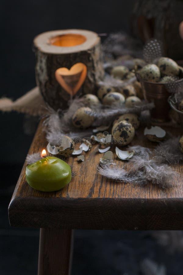 Ovos de codorniz da galinha, velas e ramos de árvore, penas e decoração para a Páscoa Copie o espaço imagens de stock royalty free